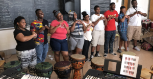 young people posing for a photo among instruments