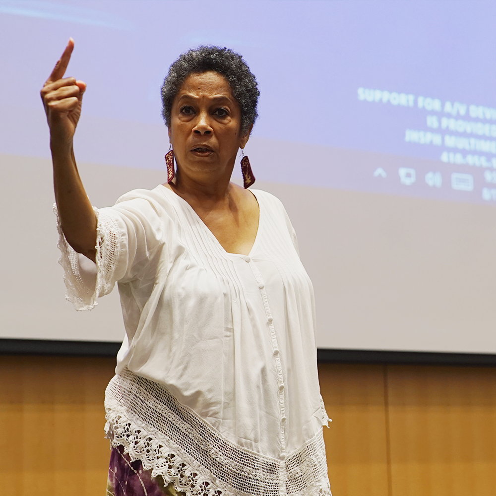 woman speaking to an audience at community event