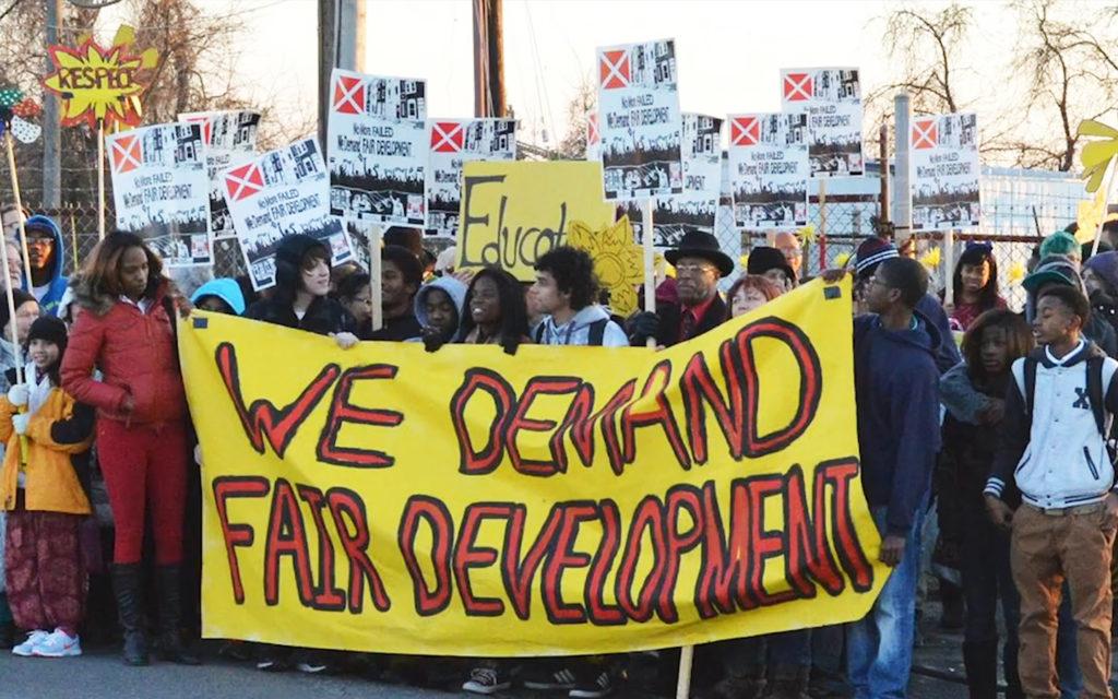 group of protestors demanding fair development