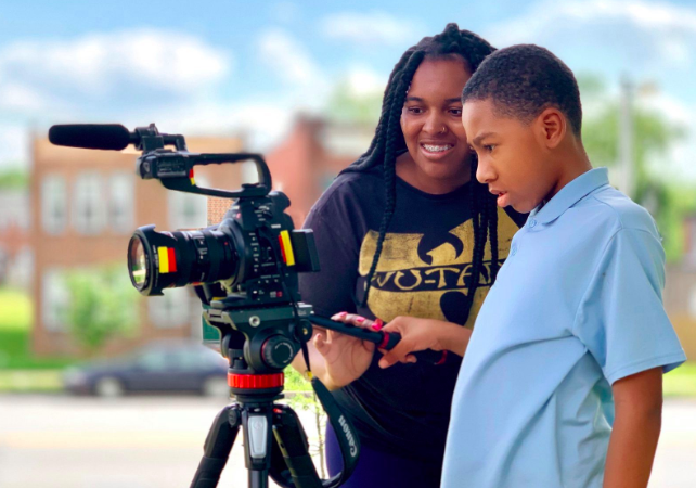 two young people operating a video camera